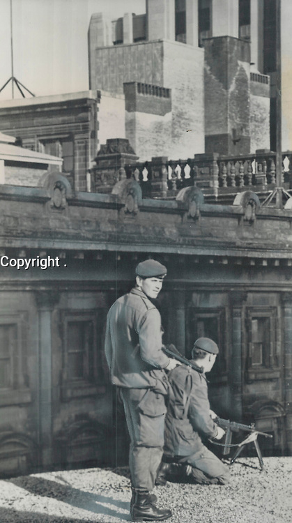 1970 FILE PHOTO - ARCHIVES -<br /> <br /> Training a Machine-Gun on the crowds below; soldiers stand guard on a rooftop while dignitaries arrive at Notre Dame Church for the funeral of murdered Pierre Laporte. Officials feared the Front de Liberation du Quebec might attempt to set off bombs in and near the church; and imposed strict security on area.<br /> <br /> 1970<br /> <br /> PHOTO : Graham Bezant - Toronto Star Archives - AQP