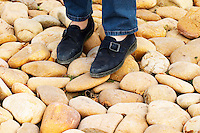 A person, two feet, standing on the typical soil in Chateauneuf, big stone pebbles called galet galets  Chateau de Beaucastel, Domaines Perrin, Courthézon Courthezon Vaucluse France Europe