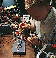 An electrical engineer solders ignition-system circuits. Ford Motor Company, Dearborn Michigan, 1966. Photo by John G. Zimmerman.