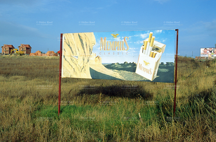 Kosovo. Pristina. A billlboard used for Memphis Classic as  advertisement. Memphis Classic is a brand of american cigarettes. New houses unbder construction. © 2001 Didier Ruef