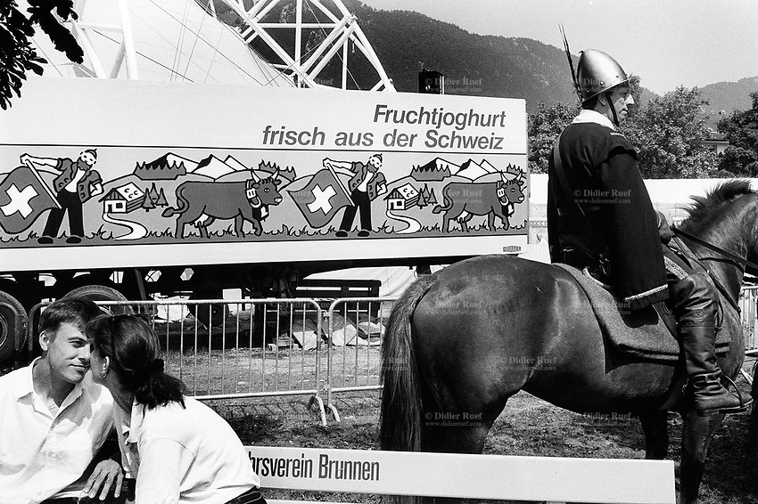 Switzerland. Canton Schwyz. Brunnen. A flirting couple, seats on a wooden bench. A horseman, dressed as an antique warrior, is getting ready for the parade during the national costume festival which is a real traditional Swiss celebration.  A truck is parked and the lorry's towing shows a large advertisement for fresh yoghurt with an alpine countryside landscape, a farm and cows in meadows, a peasant with traditional clothes throwing a swiss flag. The tent was designed by the swiss architect Mario Botta for the 700th anniversary of the founding of the Swiss Confederation. © 1991 Didier Ruef