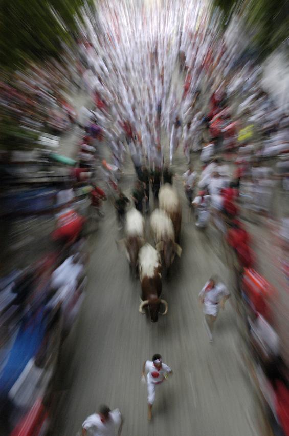 Participants run ahead of fighting bulls during a San Fermin bullrun 07 July 2007 in Pamplona..SAN FERMIN BULL RUN IRUÑA BASQUE COUNTRY ANDER GILLENEA