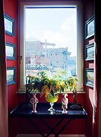 At one end of the dining room, which is decorated in warm, earthy terracotta, a vintage Murano glass urn by Venini sits atop an ebonized tray by Ilaria Miani. The recessed window looks out toward Gianicolo, one of the Seven Hills of Rome.