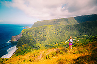 A woman with a camera pauses during a hike into Pololu Valley, North Kohala, Big Island of Hawaiʻi.