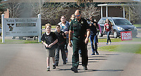 Kelly.Jordan@jacksonville.com--030812--A member of the Nassau County Sheriff's Office escorts a group of Yulee Middle School students to their anxious parents who wait at the fence after the school was put on lockdown following reports of a gun on campus Thursday morning, March 8, 2012. Nassau County Sheriff's Officers responded to the school locked it down and searched the school and found no weapons.  There were tense moments for many parents as they gathered outside of the school for information and to pick up their children.(The Florida Times-Union, Kelly Jordan)