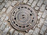 An iron manhole cover in a cobblestone street of Veliko Tarnovo, Bulgaria