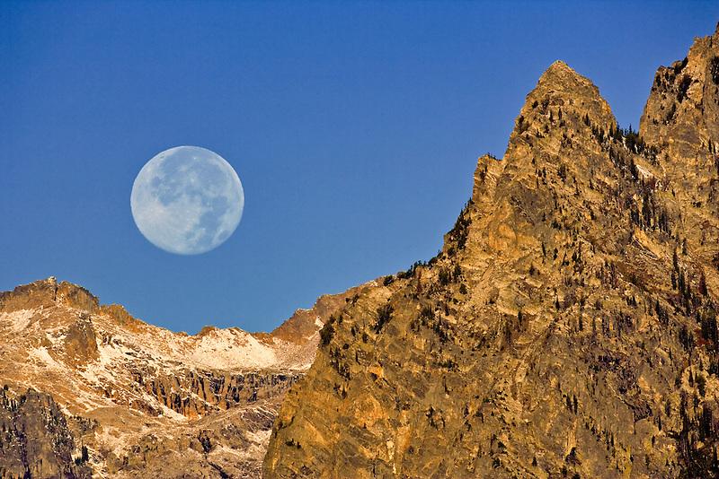 Full moonset over Teton Mountains. Grand Teton National Park, WY