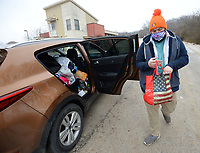 Ryan Tinsley, vice president and homeless outreach coordinator for MayDay Community Kitchen, hands out food, blankets, hand warmers, tents, gloves and other cold weather gear Friday, Feb. 12, 2021, at the Safe Camp community in south Fayetteville. 7 Hills Homeless Center, which oversees Safe Camp, was allocated $50,0000 from Fayetteville's Community Development Block Grant program to operate a cold weather response for people experiencing homelessness. Visit nwaonline.com/210214Daily/ for today's photo gallery. <br /> (NWA Democrat-Gazette/Andy Shupe)