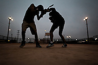 Peruvian youths workout at a sparring session during the dusk at the Boxeo VMT boxing club in an outdoor gym in Lima, Peru, 3 July 2013. Boxeo VMT is a grassroots organisation offering boxing lessons to youth as an alternative to gang violence, crime and drug-trafficking. Located in some of Lima's most marginalized neighborhoods, Boxeo VMT club joins nearly 50 young men. Although the club disposes only of an unequipped outdoor facility with couple of punching bags, the young boxers train hard three times a week and dream to become a boxing champion.