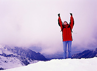 Female at the top of a winter mountain with her arms in the air.