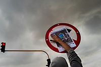 A radical student of the Universidad Nacional de Colombia attaches a poster to a traffic sign during a protest march against government's policies and corruption within the public educational system in Bogotá, Colombia, 24 October 2019.