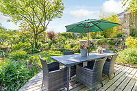 BNPS.co.uk (01202 558833)<br /> Pic: Strutt&Parker/BNPS<br /> <br /> Pictured: Garden terrace. <br /> <br /> An 18th century cottage in 'the prettiest village in England' is on the market for £675,000.<br /> <br /> Number 2 School Lane is Grade II listed, built with beautiful Cotswold stone and filled with character features like exposed timber beams and original fireplaces.<br /> <br /> The attractive three-bedroom property is in the highly sought after Wiltshire village of Castle Combe.<br /> <br /> The quintessentially English village has been used regularly as a film location and the houses are mostly made with honey-coloured Cotswold stone.