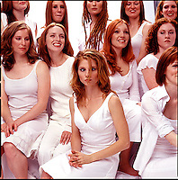 Woman crossing eyes amongst group of red haired women wearing white clothes<br />