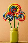 Lollipops in green vase with warm window light
