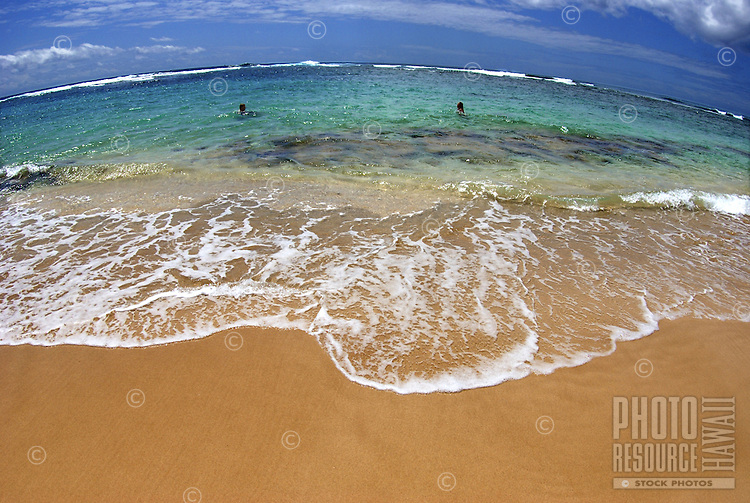 Haena shoreline, Tunnels Beach, a gentle wave washes ashore, Kauai