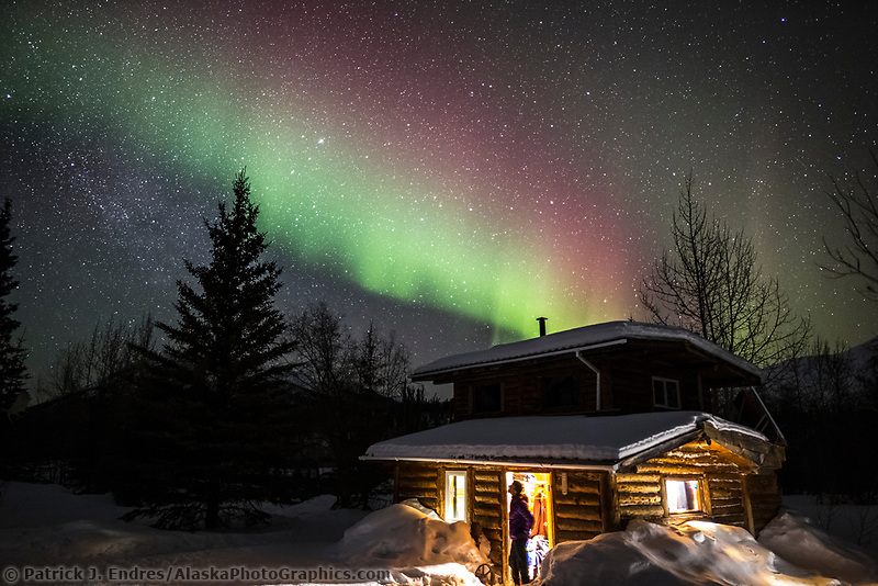 Man views the northern lights from a log cabin in Wiseman, Alaska.
