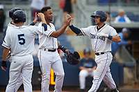 Charlotte Stone Crabs catcher Brett Sullivan (8) is congratulated by his teammates as he returns to the dugout after hitting a home run in the bottom of the seventh inning during the first game of a doubleheader against the Tampa Yankees on July 18, 2017 at Charlotte Sports Park in Port Charlotte, Florida.  Charlotte defeated Tampa 7-0 in a game that was originally started on June 29th but called to inclement weather.  (Mike Janes/Four Seam Images)