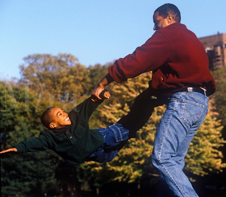 Father spins his son through the air.
