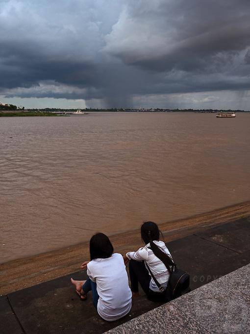 Monsoon Season in Phnom Penh. School children watching the rain storm over the Mekong. A heavy rainstorm over the Mekong River Cambodia