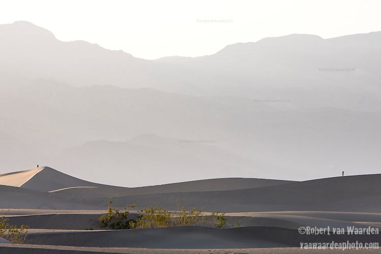 Two figures stand on the Mesquite Sand Dunes, Death Valley, California.