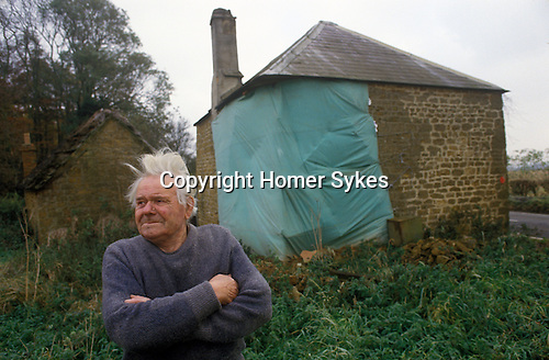 Great Tew Oxfordshire 1980s. Local resident Frank Salt who lives n the Toll House. Exterior Toll House showing damage.