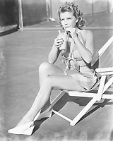 Young woman sitting on sling chair, sipping a drink