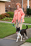 Older red headed attractive female trains her dog to walk  beside her in beautiful residential area in Spring in New Orleans