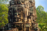 Limestone Buddha face and jungle in Bayon Temple in the famous, ancient UNESCO heritage Khmer Angkor Wat temple, Siem Reap, Cambodia Southeast Asia