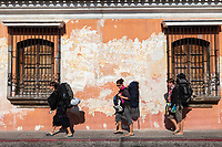 Antigua, Guatemala.  Three Women Backpackers Walk Past an Old House with Flaking Paint.