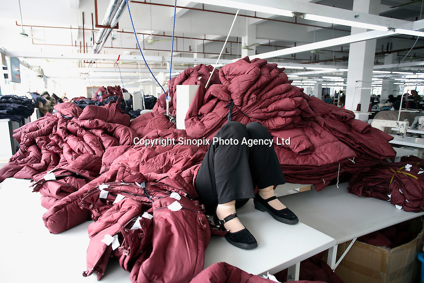 A worker sleeps under a pile of coats during a lunch break at the Quanli Garment Factory in Pinghu, Zhejiang Province, China.  It is a normal practice for factory workers to sleep during lunch breaks in China. The textile industry in China suffers severe difficulties since 2008. Its export was 185.17 billion U.S. dollars in 2008, up 8.2 percent year-on- year, but the growth rate was 10.7 percentage points lower than in 2007..