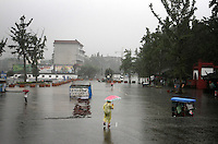"""A rainstorm engulfs visitors outside the entrance to the Dujiangyan Irrigation System. The system is regarded as an """"ancient Chinese engineering marvel."""" By naturally channeling water from the Min River during times of flood, the irrigation system served to protect the local area from flooding and provide water to the Chengdu basin. Sichuan Province. 2010"""