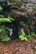 A hiker exits an old mine tunnel on Iron Mountain during the summer months in Jackson, New Hampshire USA. This tunnel is about 50 feet long.