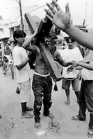 Philippines. Luzon island. San Fernando, Pampanga.70 km from Manila. Flagellation at Easter on Good Friday. A masked man carries a heavy wood cross. He receives from some friends a small plastic bag filled with water to be drunk. © 1999 Didier Ruef