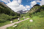 Caucasian female hiking along Maroon Creek towards the Maroon Bells Peaks, Aspen, Colorado, USA