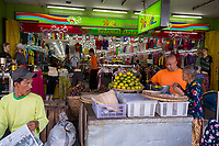 Yogyakarta, Java, Indonesia.  Buying Oranges at a Sidewalk Fruit Stand in front of a Clothing Store, Malioboro Street.