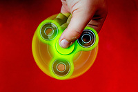 Bright Green fidget spinner in use over a red background