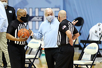 CHAPEL HILL, NC - FEBRUARY 24: Head coach Roy Williams of North Carolina talks with officials Brian Dorsey and Lamar Simpson during a game between Marquette and North Carolina at Dean E. Smith Center on February 24, 2021 in Chapel Hill, North Carolina.