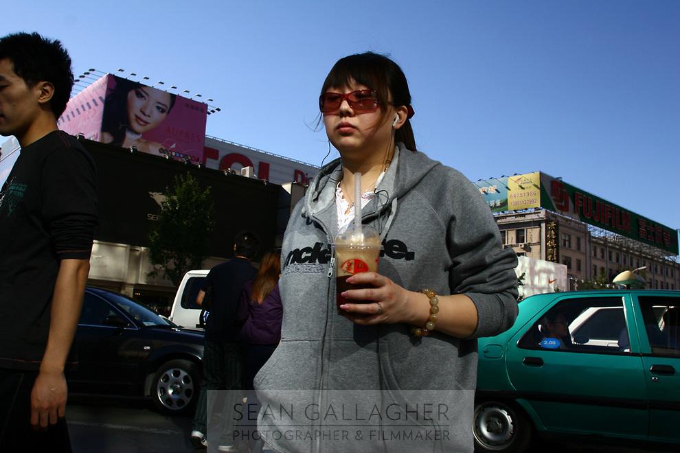 CHINA. Beijing. A shopper on the Wangfujing shopping street in central Beijing. 2006.