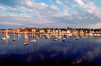 Seascape of Rockport Harbor with sailboats moored under a cloudy, wide, summer sky. Rockport, Cape Ann, Massachusetts.