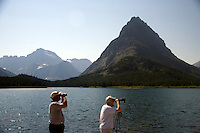 People use binoculars to look at wildlife near Swiftcurrent Lake near the Many Glacier Hotel in Glacier National Park in Montana.
