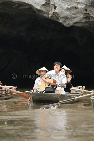 Asia, Vietnam, Tam Coc near Ninh Binh. Boat trip at Tam Coc (Three Caves). To visit the Three Caves (Tam Coc) tourists are punted in metal boats along the watery landscape and through three long caves. At some places these are so low that peope have to duck, while boat people propel the boat by pushing on the cave roof with their hands.