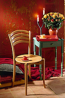 A light wood chair stands next to a green painted table. On the table is a flower arrangement of roses, a candlestick and a tray with cups.
