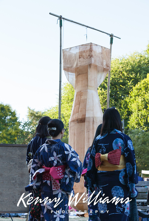 """Asian women performers dressed in beautiful blue kimonos and """"Little Boy, Folded"""" atomic bomb sculpture. From Hiroshima to Hope 2015, Seattle, Washington State, WA."""