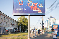 """SARANSK, RUSSIA - June 25, 2018: Pedestrians walk by a """"Welcome to Saransk"""" sign before the 2018 FIFA World Cup group stage match between Iran and Portugal."""