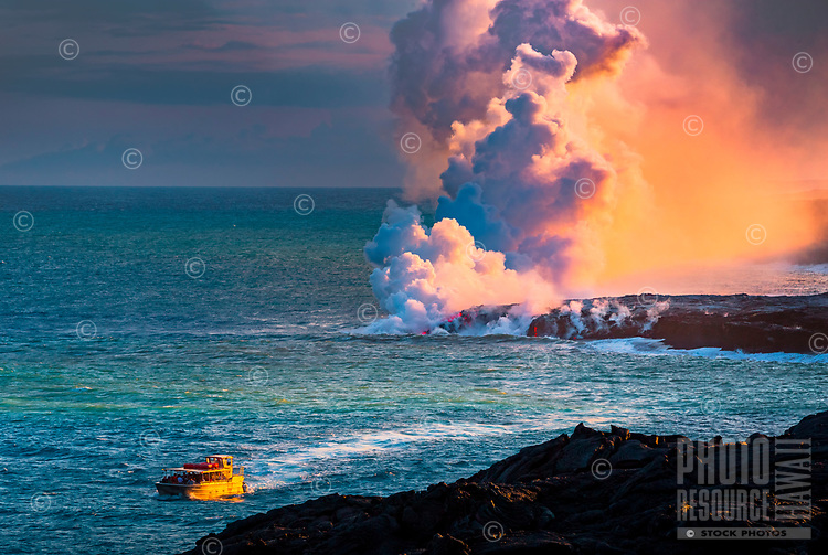 A sightseeing tour boat hugs the coast of Hawai'i Volcanoes National Park, with the Kamokuna lava flow's entry point behind it, Big Island of Hawai'i.