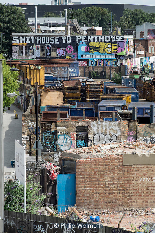 Gentrification in east London. Graffiti and wall art on an empty building awaiting demolition in Hackney Wick, a rundown area of warehouses, small industrial units and tenement blocks next to the Olympic Park.