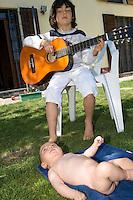 homeschooling, educazione parentale, educazione domestica.Concerto alla chitarra di Thomas, sette anni, per suo fratello Benjamin di 2 mesi.