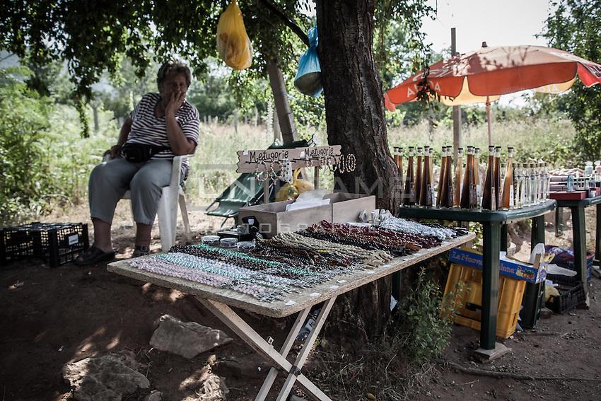 A souvenir and rosaries vendor stall. Many vendors on the pathway between Bijakovici and Medjugorje are of Muslim faith.<br /> Bijakovici, Medjugorje, Bosnia and Herzegovina. July 2012