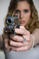 Caucasian blonde woman pointing handgun<br />