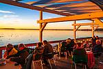 Deutschland, Bayern, Chiemgau, Chieming am Chiemsee: Betrachten des Sonnenuntergangs vom Restaurant und Café 'Haus am See' | Germany, Bavaria, Chiemgau, Chieming at Lake Chiemsee: watching sunset at restaurant and café 'Haus am See'